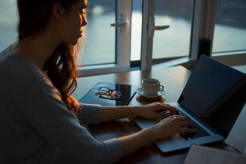 暗闇でパソコンを使って作業する人
