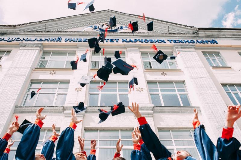 学帽を空に向かって放り投げる学生たち