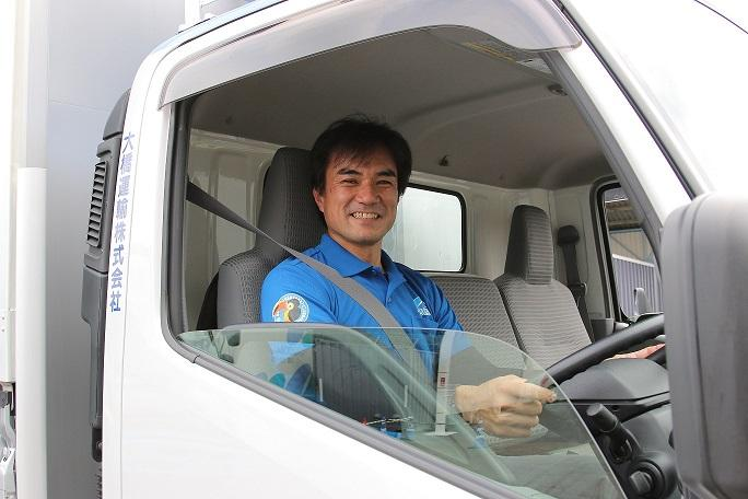 トラックの窓から顔を出す大橋運輸のドライバー