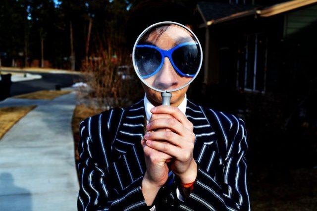 虫眼鏡をもつ人の画像