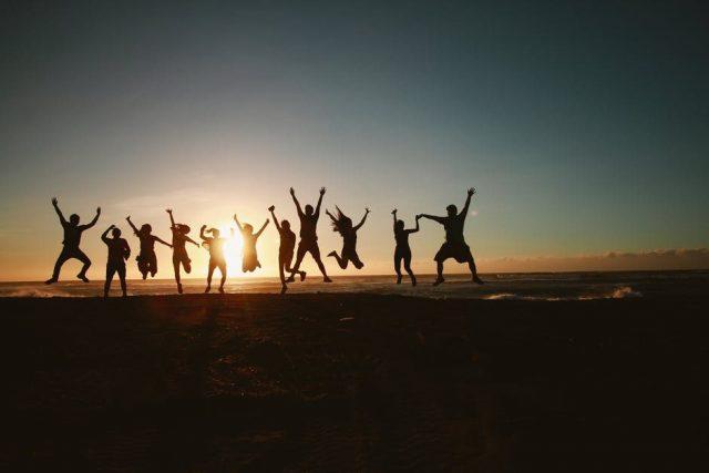 11人が朝焼けにむかって飛び上がっている画像
