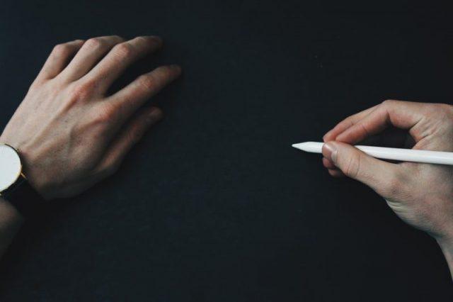 手とペンの画像