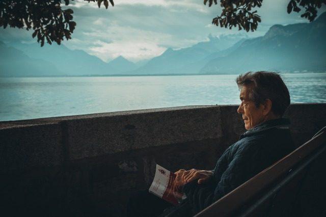 ご老人が湖のほとりで読書する様子