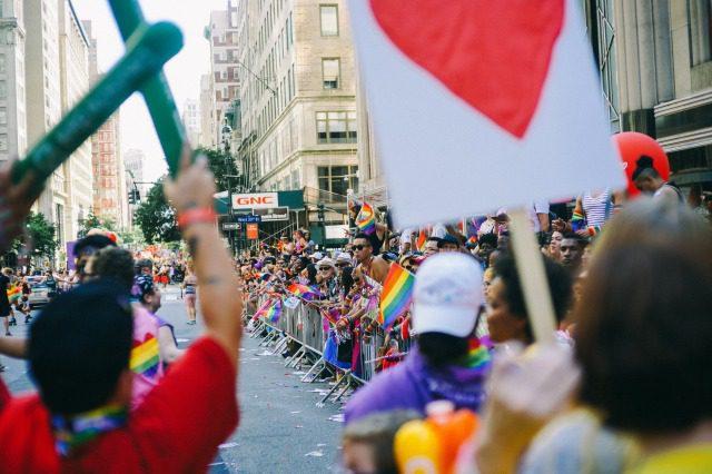 たくさんの人がレインボーフラッグを掲げながらパレードに参加する様子