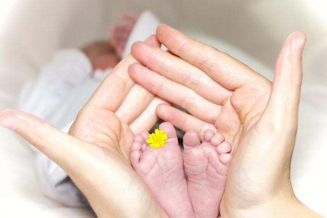 寝ている赤ちゃんの足を優しく包む手のひら