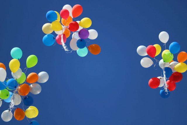 青空に向かってたくさんの風船が飛んでいく風景