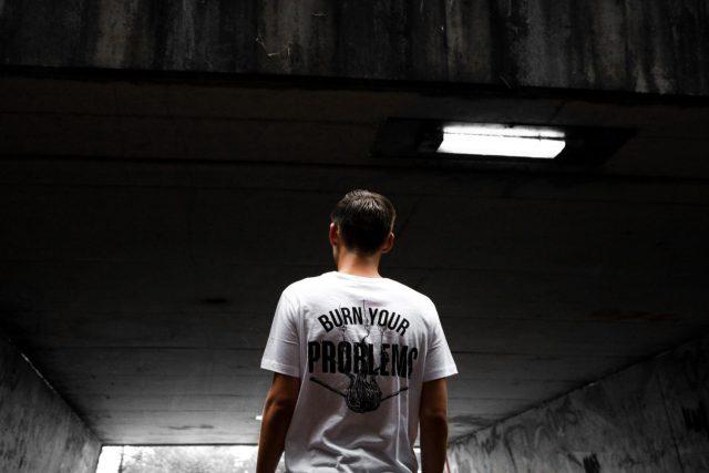 「Burn your problems」と書いてあるTシャツを着た人が薄暗いトンネルに入っていく様子