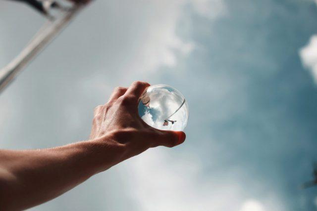 透き通った水晶を空にかざしている様子
