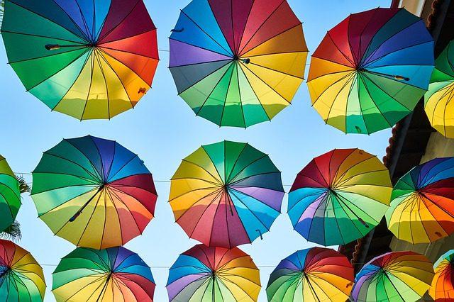 たくさんの虹色の傘が開かれて、並んで吊るされている様子