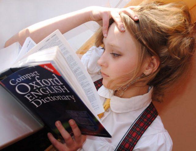 頭を抱えながら本を読んでいる人