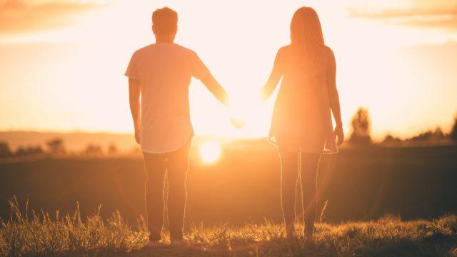 夕日を見ながら手を繋ぐカップルの後ろ姿