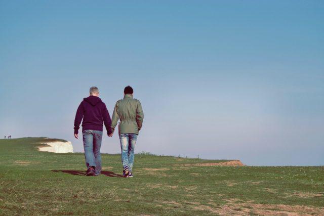 手を繋いで野原を歩くゲイカップルの後ろ姿