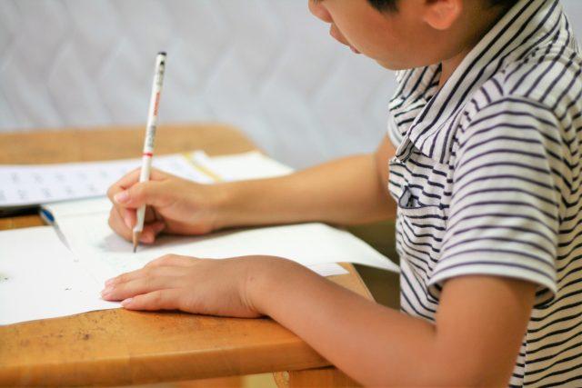机に向かう日本人の子ども