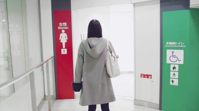 女性用トイレを前にする人