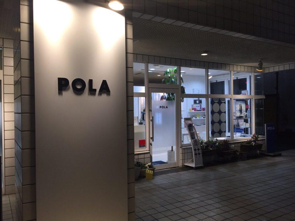 POLAくずは店の外装。シンプルな白い看板にPOLAの文字が照らされている。ガラス張りの店舗