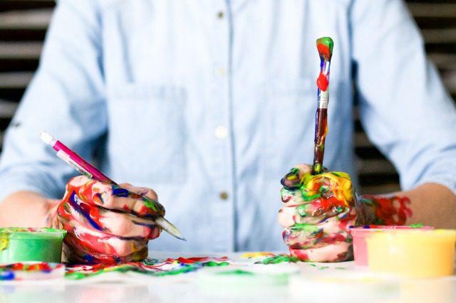 カラフルな絵の具だらけの手でペンと筆を持ち、絵を描いている様子
