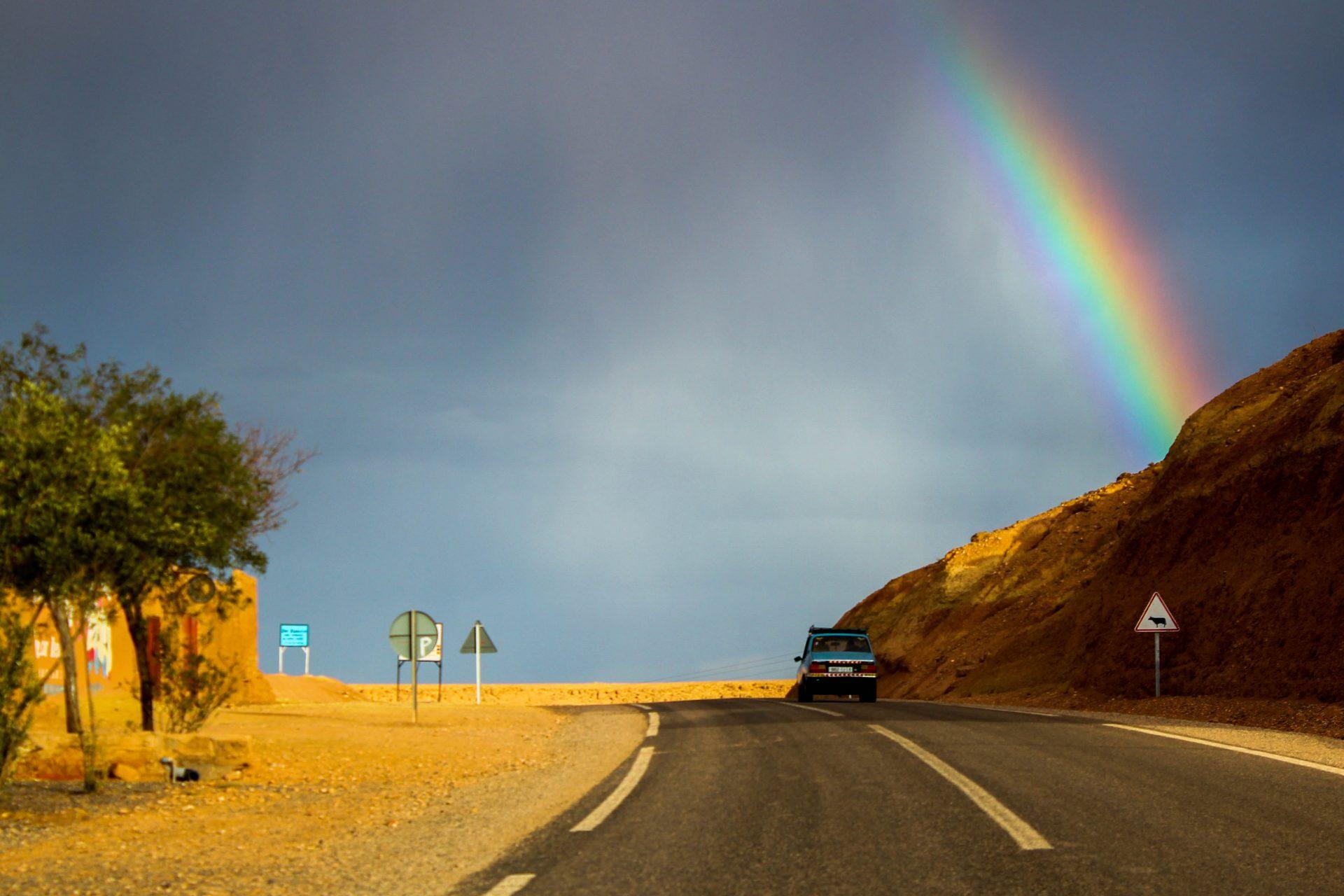 荒野の間を通る道路の上に虹がかかる様子