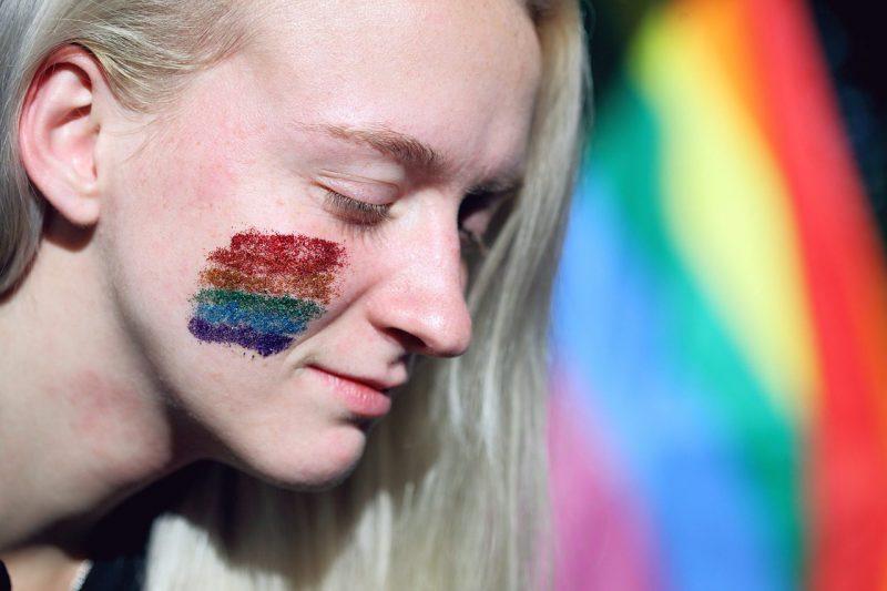 頬に虹のペイントをした女性の画像
