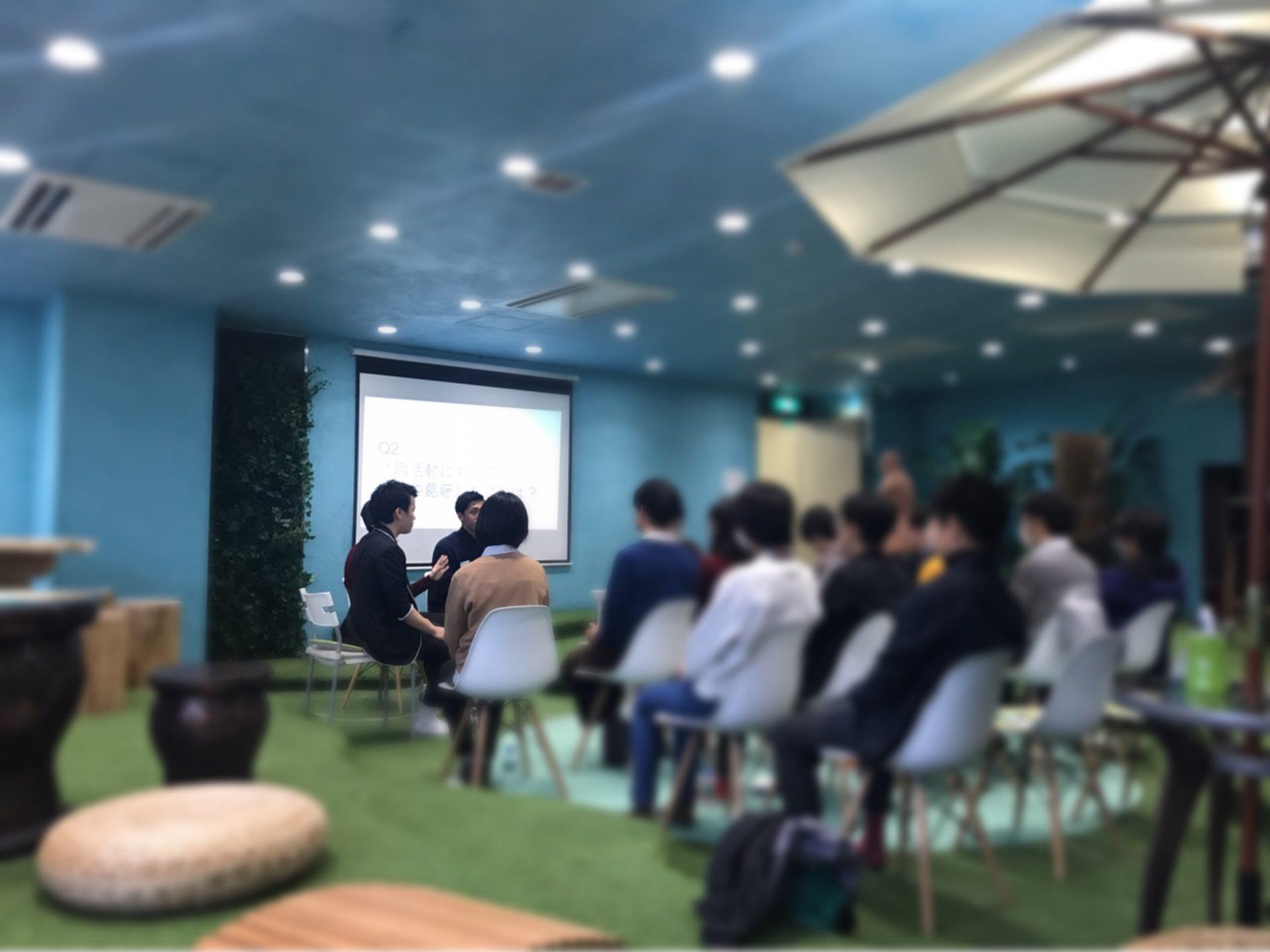 会場にて、開放的な空間で社員を囲みながら座る参加生の様子