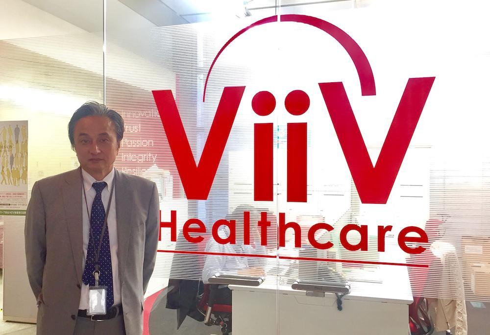 ヴィーブヘルスケア株式会社のロゴの横に立つ入山さん