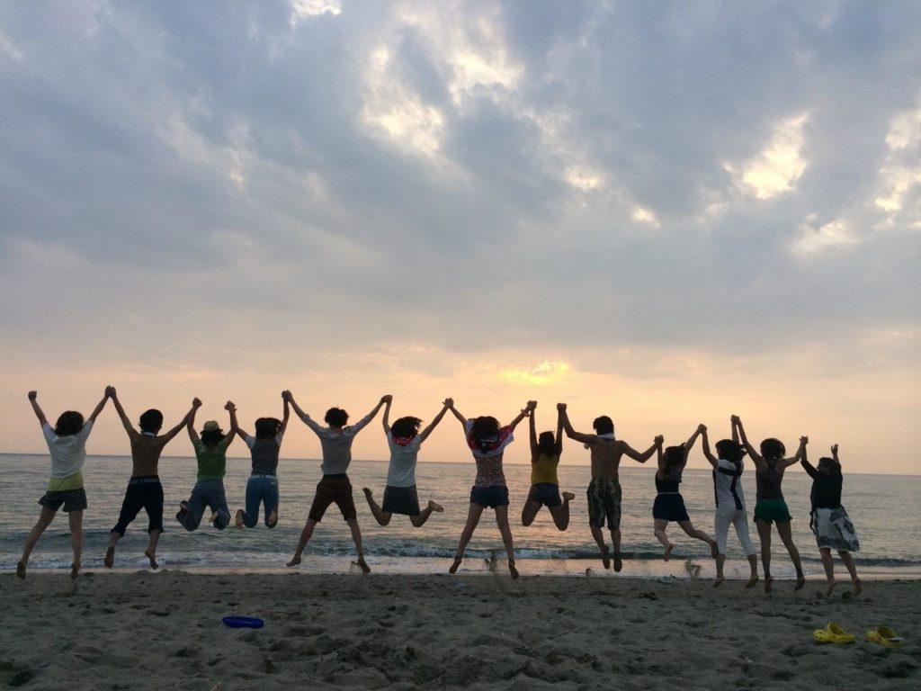 秋田の海で一斉にジャンプするグローヴの社員