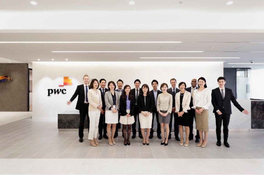 PwCのオフィス前で集合写真をとるPwCの社員たち