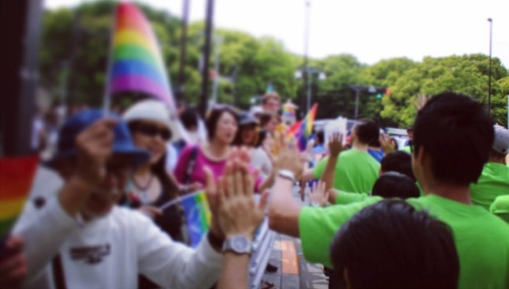 東京レインボープライドで、GLEAMの人たちが沿道の人たちとハイタッチしている画像
