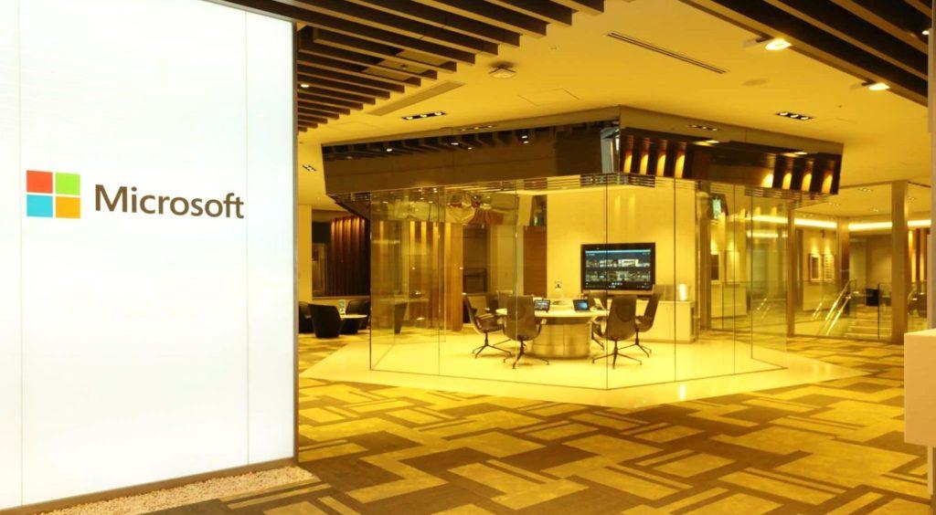 ガラス張りの会議室と、マイクロソフトのロゴが書かれた看板の画像