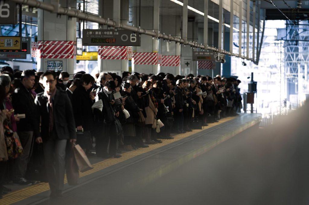駅のホームで多くの人が電車を待っている画像