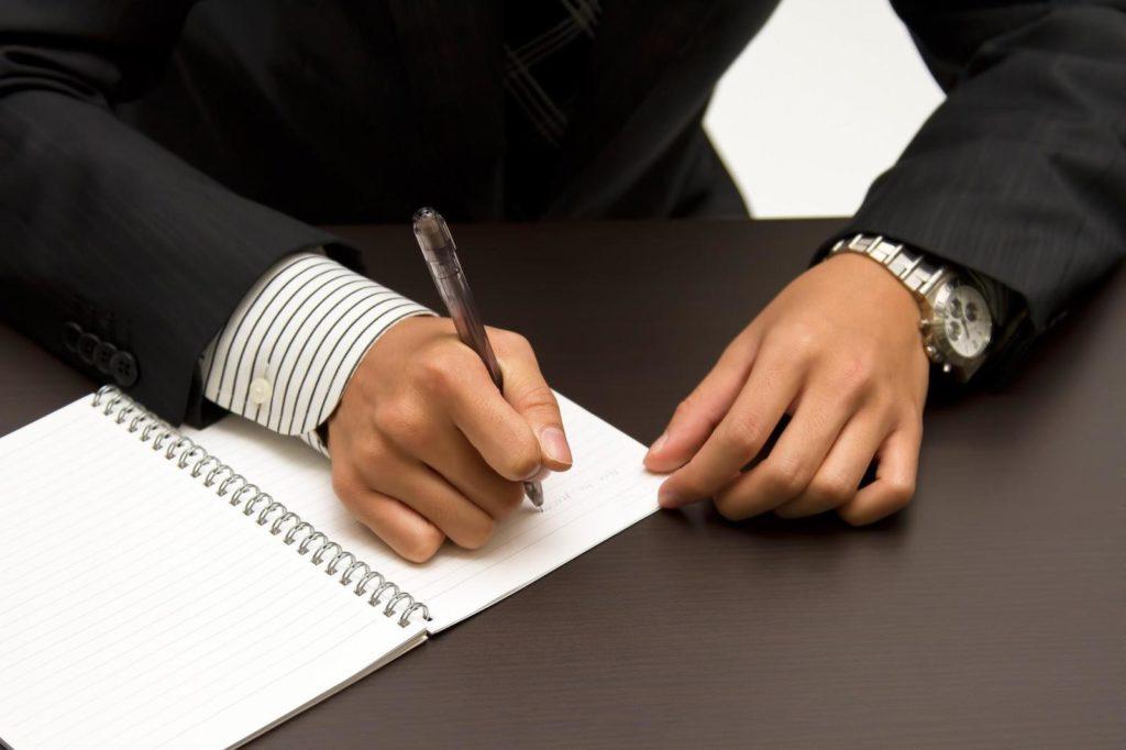ノートに書き込むビジネスパーソンの手元の画像