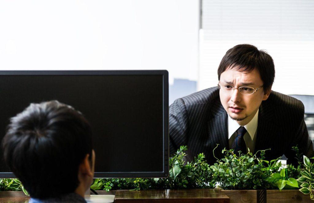 パソコンの画面越しに何かを言おうとしているビジネスパーソンの画像