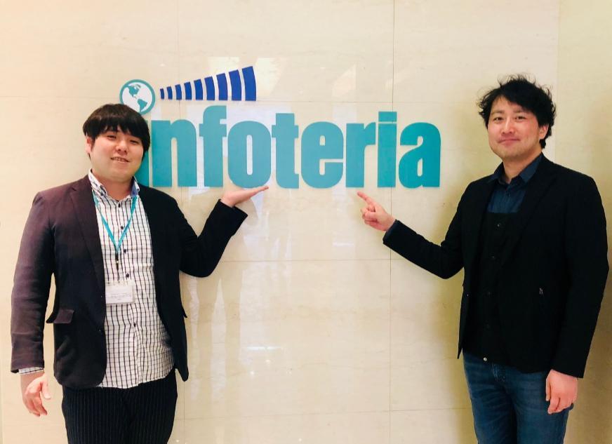 長沼さんと高橋さんが、インフォテリアのロゴに手を添えている画像