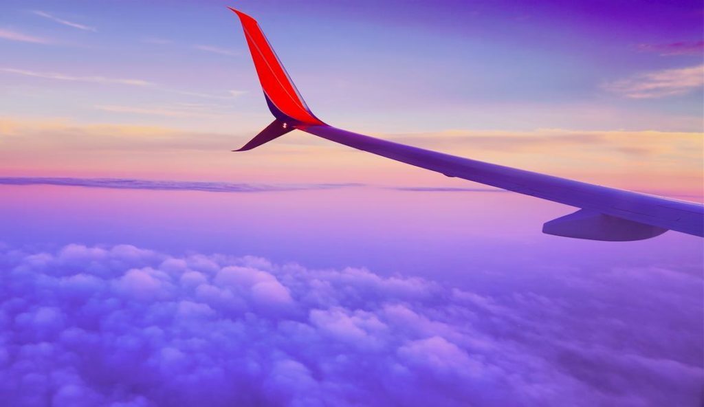 雲の上を飛ぶ飛行機の左翼の画像