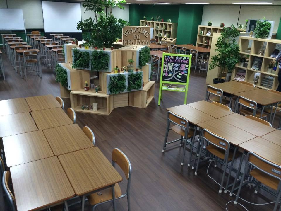 多くの机と椅子が並ぶ、賢者屋の中の画像