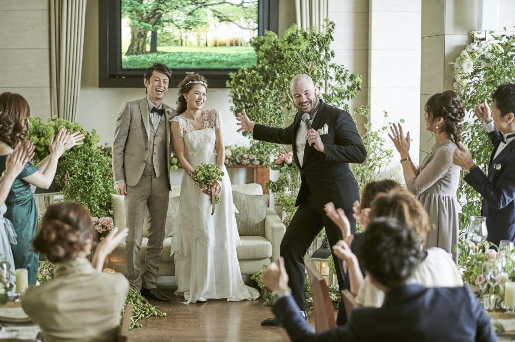 結婚する二人が外国人風の司会に紹介され、参列者に拍手されている画像(イメージ)