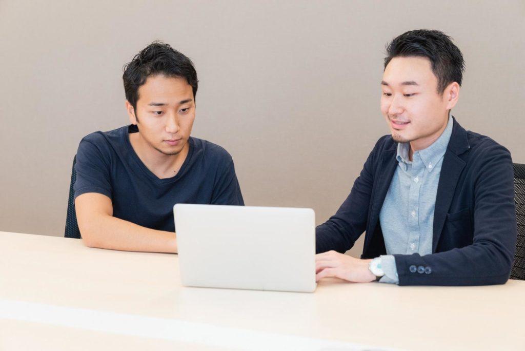 堀江さんとタケマルさんがパソコン画面を見ている画像