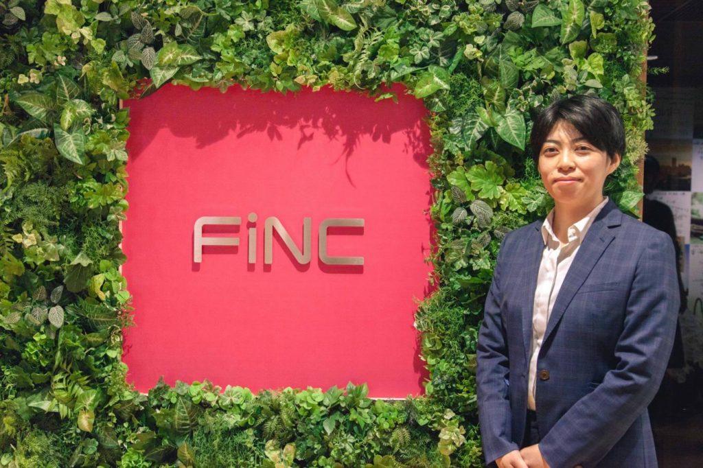 FiNCのロゴの横に立つ井上さんの画像