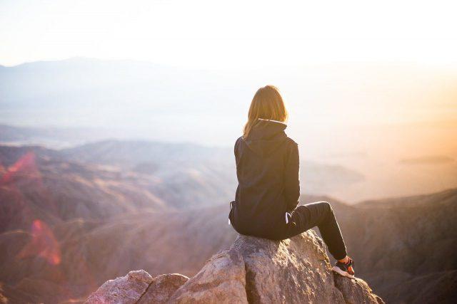 高い岩山の上に座る人