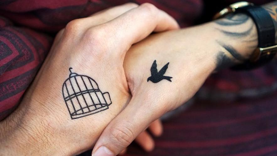 鳥と鳥かごのタトゥーが入った二人の手の写真