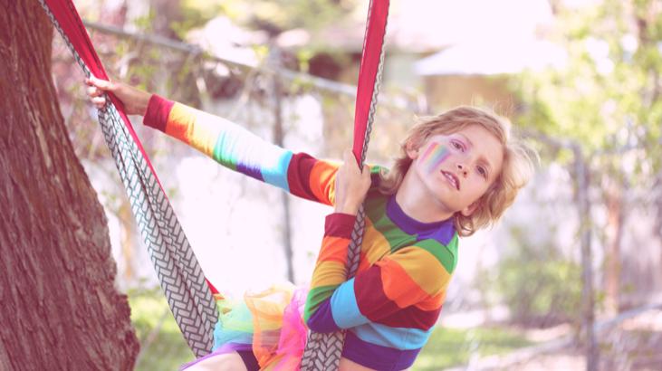 虹色のフェイスペイントをして外で遊ぶ子供