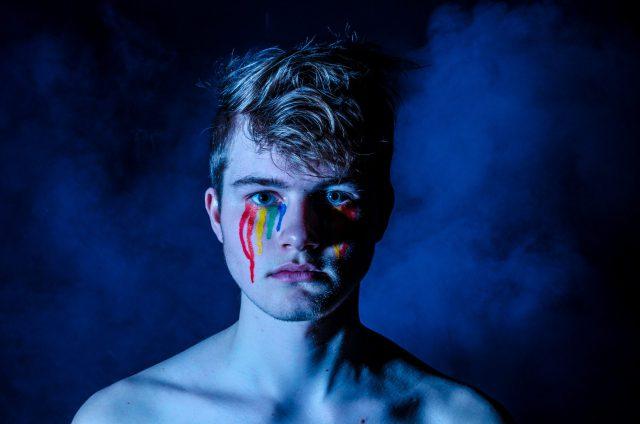 目から涙が出ているような虹色のペインティングをしている人の画像