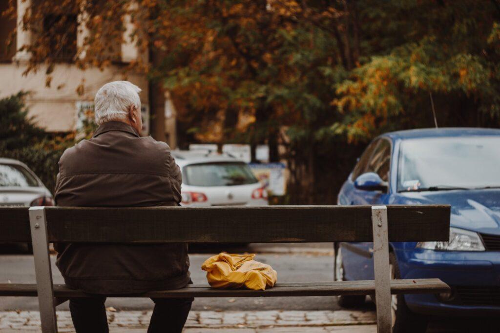 ベンチに1人で腰掛ける老人