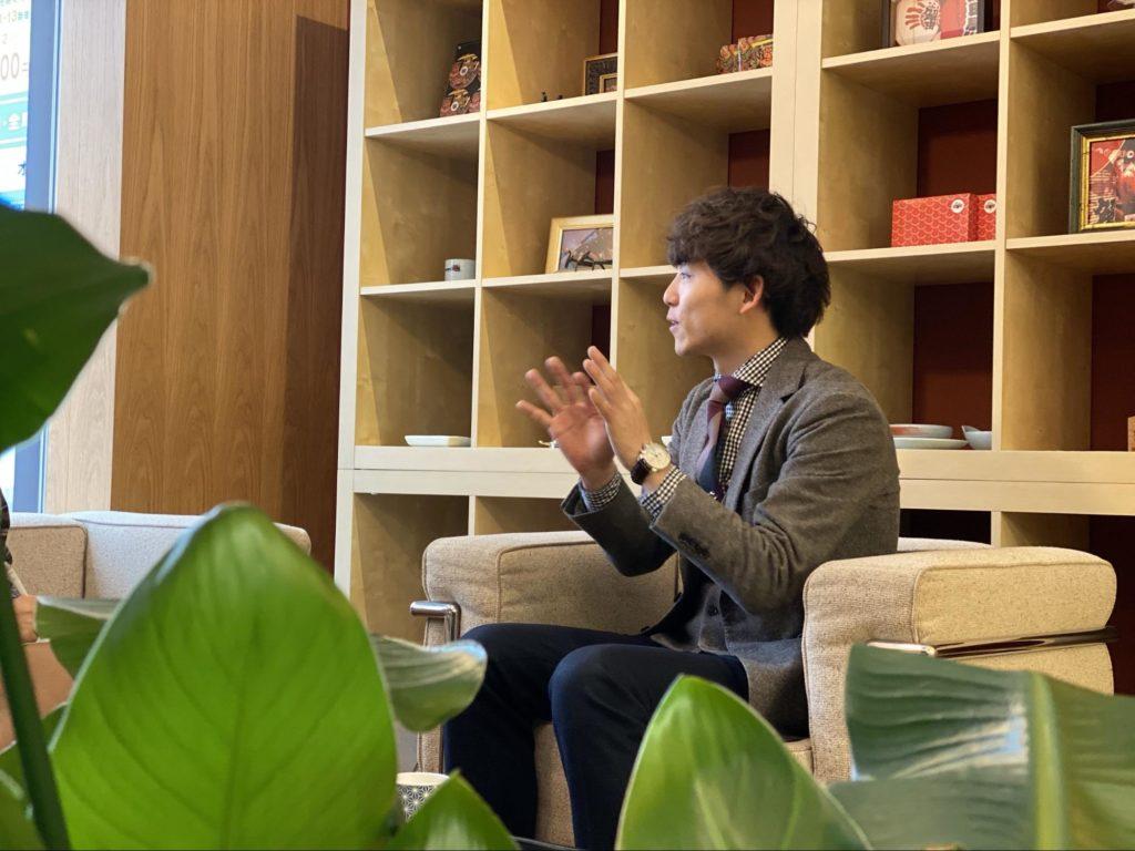 オフィスでインタビューに答える田中さん