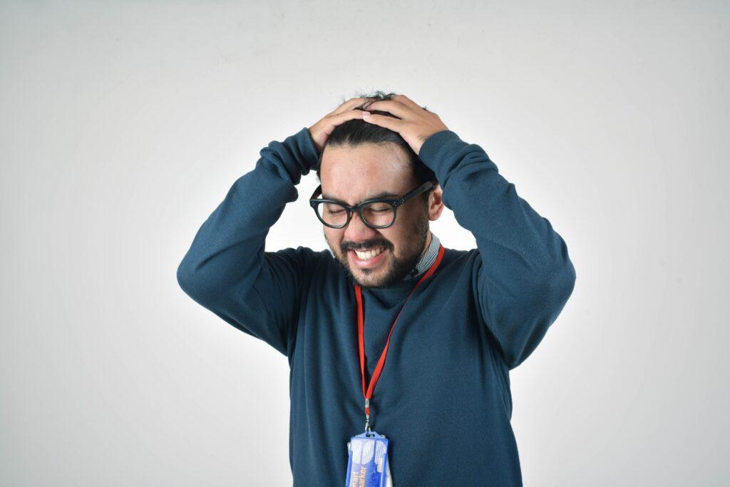 頭を抱えるメガネの人