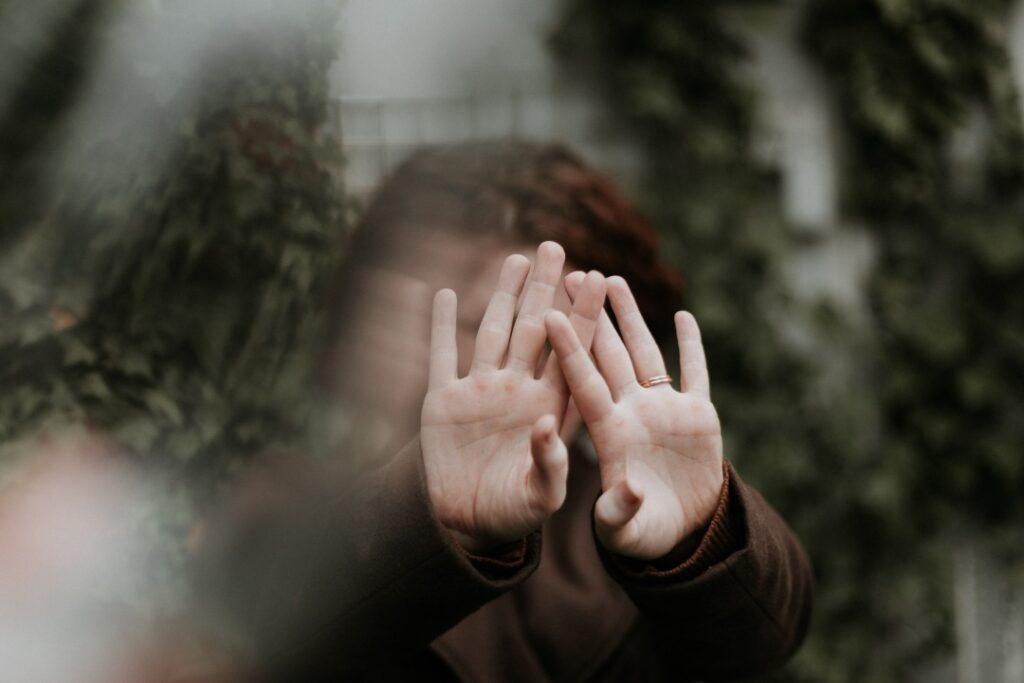 両手で顔を覆い隠す人