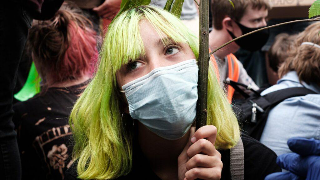 フラッグを持ちマスクをつけた人